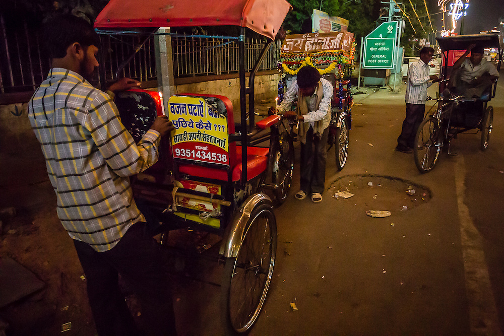 Two rickshaw drivers light up candles for celebration of Dowali, the Hindu festival of Light