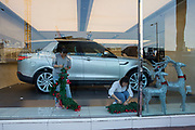 Shop workers setting up Christmas decorations in a Range Rover showroom on 10-13 Sino Plaza, Gloucester Road, Causeway Bay, Hong Kong.  (photo by Andrew Aitchison / In pictures via Getty Images)