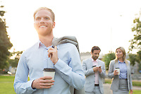 Happy businessman holding disposable cup with colleagues standing in background