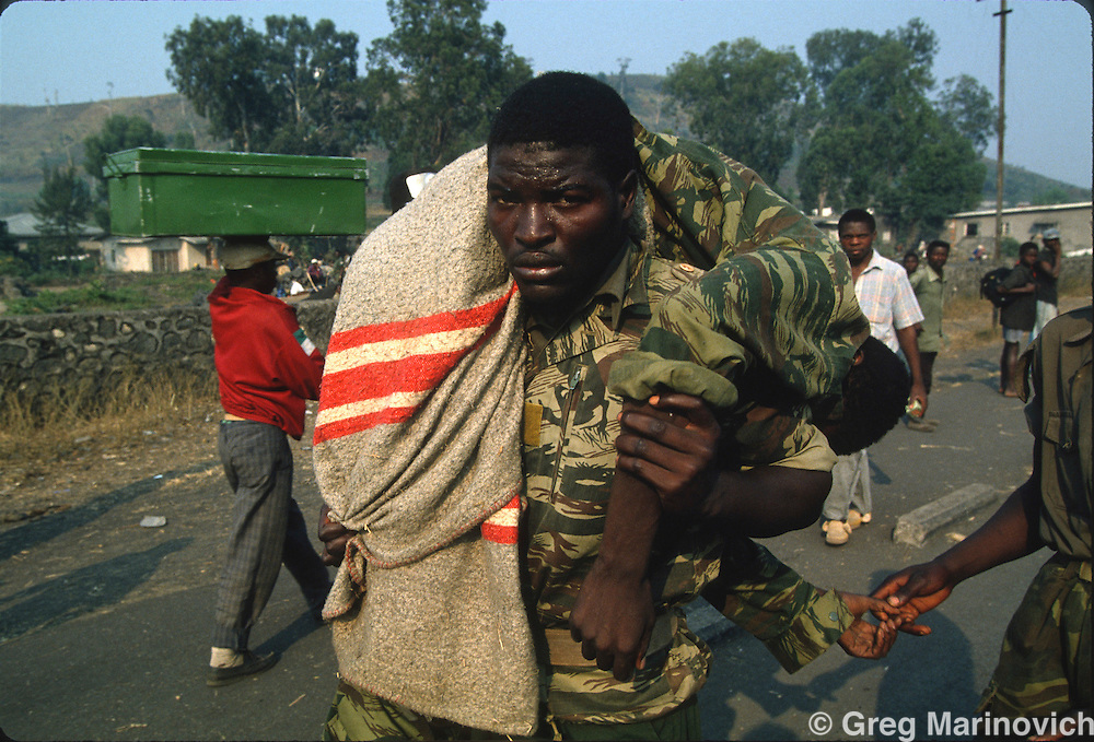 Goma, Zaire, A Rwandan Hutu soldier carries a comrade struck down by cholera in Eastern Zaire after the army, militia escaped an RPF takeover that followed and stopped the genocide of Rwandan Tutsis and Hutu moderates by extremist Hutus. 1994. Greg Marinovich