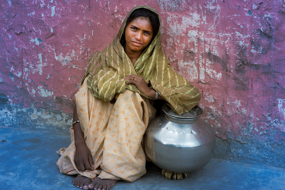 Traditionally dressed girl with a waterpot, sitting and leaning against a mudwall.