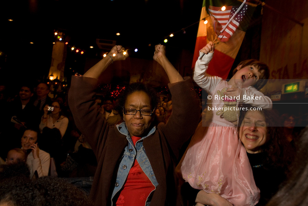 Elated US citizens celebrate at the very moment of Barack Obama's inauguration as the United States' 44th President, after his Nov 08 election victory as America's first African American Commander in Chief. Members of expatriates and 'Democrats Abroad' party supporters wave their hands in the air at The Texas Embassy Texmex bar in central London, England. Similar events were held by Democrats Abroad around the world but in England, Obama's election to the White House excited Britain's political and cultural landscape during a deep economic recession...
