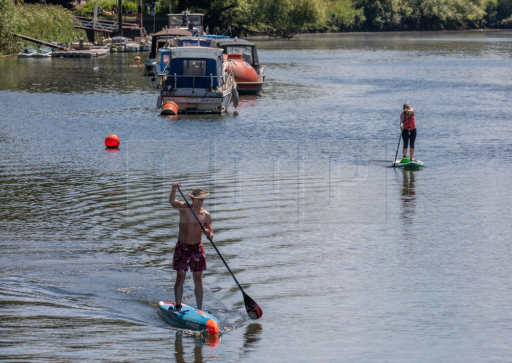 © Licensed to London News Pictures. 21/05/2020. London, UK. Paddle boarders enjoy the sunshine along the River Thames in Richmond in South West London as weather experts predict the another warm day with a high of 27c. Last week the Government eased the law on lockdown to let people spend more time outside to enjoy sunbathing and picnicking. Photo credit: Alex Lentati/LNP