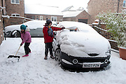 A young boy aged 11 and a girl aged 8 clear snow off the drive and parents cars outside their home in Yorkshire, UK.