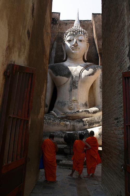 Monks visiting the gigantic seated Buddha at Wat Sri Chum, Sukhothai