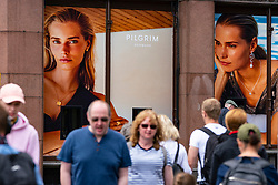 Edinburgh, Scotland, UK. 24 July, 2020. Shoppers on Princes Street waIk past window display for Pilgrim of Denmark, in Jenners department store.  Iain Masterton/Alamy Live News