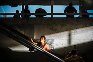Uma passageira sobe as escadas rolantes da Rodoviária do Plano Piloto no final de um dia de trabalho em Brasíla. Na parte superior do terminal, muitos motoristas de vans e carros não licenciados oferecem meios de transporte alternativos para suprir a insuficiência de algumas linhas do transporte oficial.