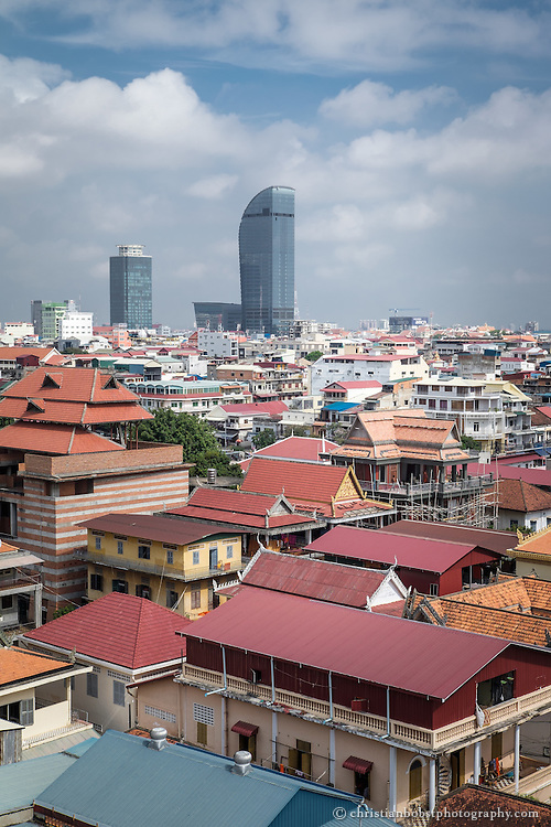 Aussicht von der Dachterasse des Frangipani Royal Palace Hotel & Spa auf die Dächer von Phnom Penh. Im Vordergrund rechts sieht man die orangen Dächer der Tempelanlage Wat Ounalom, im Hintergrund dominiert den gerade erst fertiggestellte, 188 Meter hohe Vattanac Capital Tower die Skyline der Stadt.