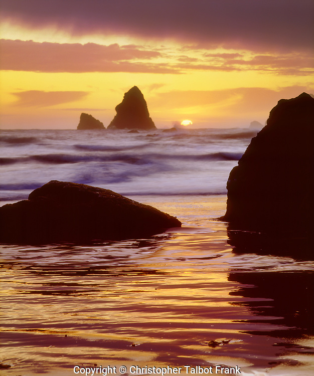 I took this photo of a sunset and sea haystacks on the Pacific Northwest coast. As the sun sets into the ocean, the colorful clouds reflect on the beach.