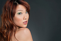 Portrait of young Chinese woman with eye shadow looking back over colored background