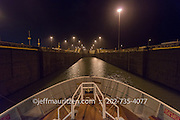 The bow of a ship as it transits the Gatun Locks in the Panama Canal at nighttime.