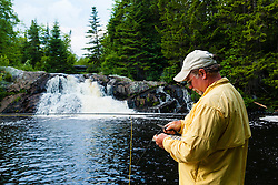 A man choosing a dry fly for fishing below Upper Cold Stream Falls in Maine's Northern Forest. Johnson Mountain Township.