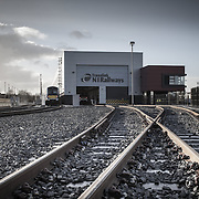 Building: Adelaide Maintenance Depot Architect: White Ink Architects Building Type: Industrial Town: Belfast County: Antrim Country: Northern Ireland Collection: Architecture The Adelaide Maintenance Depot is a purpose built facility on a brownfield site, that serves Tranlink's new fleet of trains that will be delivered in 2012. The site is a 24hr facility that will provide stabling for trains, re-fuelling and train wash facilities along with a Maintenance and Cleaning Shed and associated offices and storage. The design concept was to create a hierarchy of buildings across the site, with the Depot being the main building and all other buildings would use the same palette of materials to create a cohesive identity for the site facilities. The Depot is over 200m long and is a slick linear box clad in silver metallic cladding. The interior is bathed in diffuse daylight through translucent Kalwall cladding. The associated Accommodation Block is articulated at first floor as a projecting, floating box in distinctive red cladding. It projects at high level beyond the main shed, its dynamic form referencing the trains within. The buildings base is detailed in simple blue grey brick, that is used throughout the rest of the site for ancillary buildings. Careful detailing and co-ordination of services has ensured that the box forms are uncluttered and bold. The project is due for completion in October 2012.<br /> <br /> Adelaide Maintenance,White Ink Architects,Industrial,Architecture Photography Belfast, Architecture Photography Northern Ireland, architecture architectural interior exterior photography Belfast, architectural photographer Belfast, architecture photographer Belfast