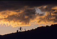 A mountain biker carries his bike up a rocky slope, silouette at sunset.