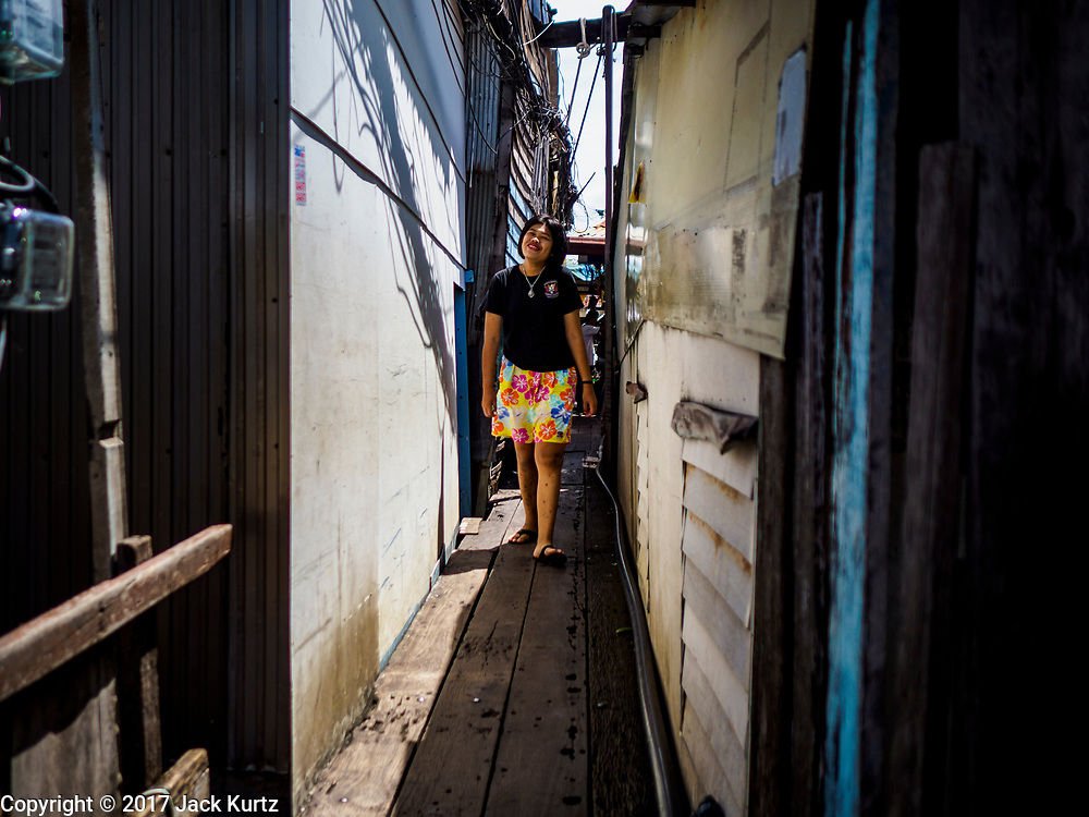 "21 JUNE 2017 - BANGKOK, THAILAND: A woman walks between homes in a community along the Chao Phraya River south of Krung Thon Bridge. This is one of the first parts of the riverbank that is scheduled to be redeveloped. The communities along the river don't know what's going to happen when the redevelopment starts. The Chao Phraya promenade is development project of parks, walkways and recreational areas on the Chao Phraya River between Pin Klao and Phra Nang Klao Bridges. The 14 kilometer long promenade will cost approximately 14 billion Baht (407 million US Dollars). The project involves the forced eviction of more than 200 communities of people who live along the river, a dozen riverfront  temples, several schools, and privately-owned piers on both sides of the Chao Phraya River. Construction is scheduled on the project is scheduled to start in early 2016. There has been very little public input on the planned redevelopment. The Thai government is also cracking down on homes built over the river, such homes are said to be in violation of the ""Navigation in Thai Waters Act."" Owners face fines and the possibility that their homes will be torn down.          PHOTO BY JACK KURTZ"