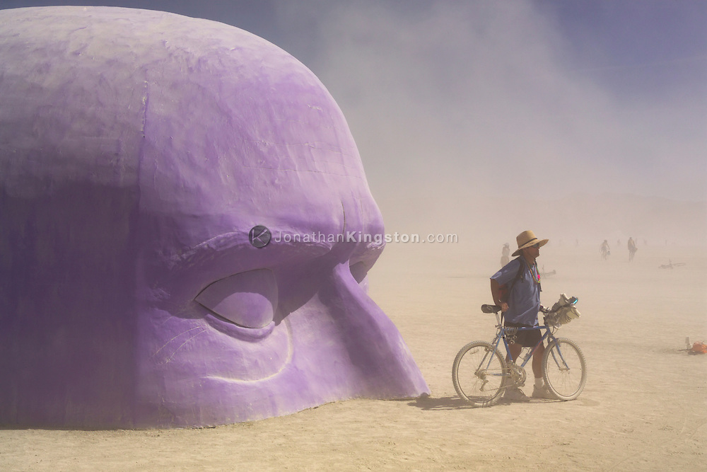 """BLACK ROCK CITY, NV:  A man stands in front of Pepe Ozan's """"Dreamer"""" during a dust storm in Black Rock City, Nevada."""