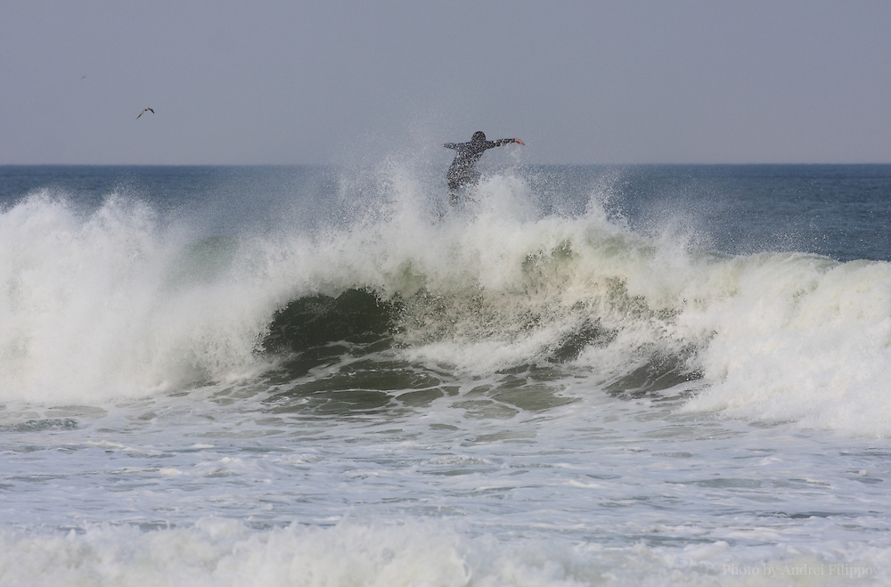Surfer losing balance on the top of the wave at the Marconi Beach, Cape Cod, Massachusetts, USA, September 3, 2011.