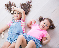 High angle view of cute little sisters lying on wooden floor at home