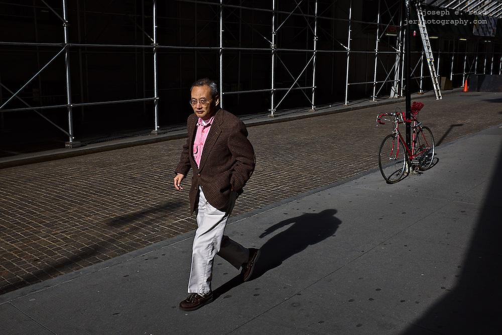 Man walking past bicycle on sidewalk, New York, NY, US