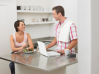 Couple in kitchen woman eating man using laptop