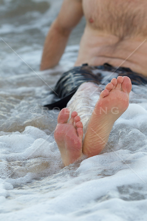 detail of a man sitting in the ocean with his feet crossed