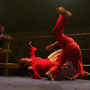 Cholita Martha La Altena fighting against El Cobarde during the 'Titans of the Ring' wrestling group who perform each Sunday at El Alto's Multifunctional Centre. Bolivia. The wrestling group includes the fighting Cholitas, a group of Indigenous Female Lucha Libra wrestlers who fight the men as well as each other for just a few dollars appearance money. El Alto, Bolivia, 24th January 2010. Photo Tim Clayton