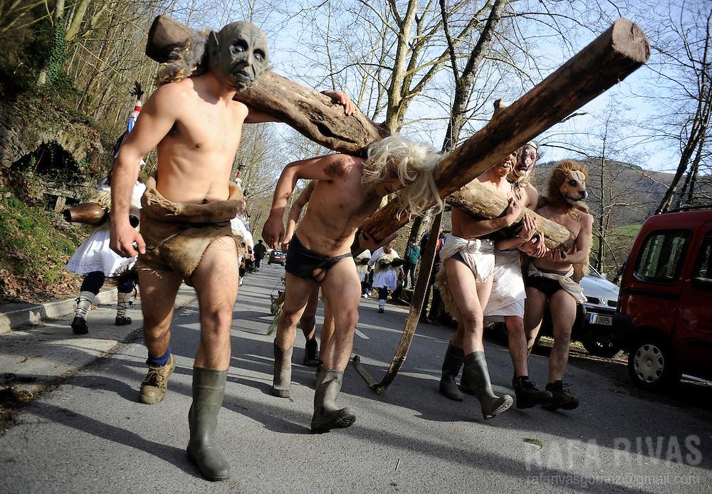 A group of masked locals carry a cross during the ancient carnival of Zubieta, in the northern Spanish province of Navarra province, on January 29, 2013.