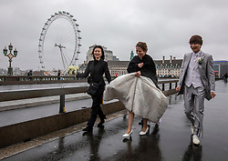 © Licensed to London News Pictures. 14/01/2020. London, UK. Wedding photos sdon't go quite to plan on Westminster Bridge as London braces for more wind and heavy rain during this evening's rush hour. While another storm heads to the South East behind Storm Brendan. Photo credit: Alex Lentati/LNP
