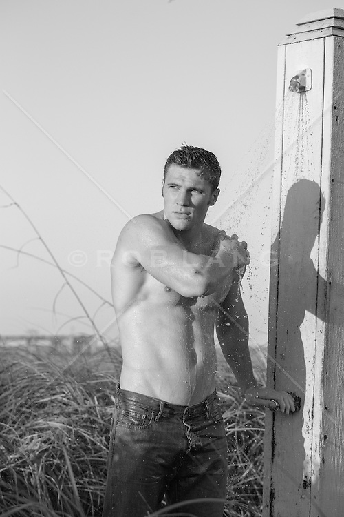 shirtless man in an outdoor shower by the ocean