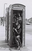 Teenagers in a phone box. London, Greenford, UK, 1980s.