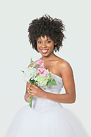 Portrait of beautiful African American bride holding bouquet over gray background