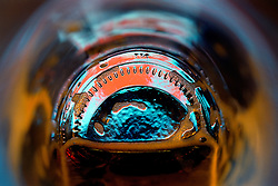 """Beauty at the Bottom: Beer Rise""- This image is a photograph of a beer bottle shot right down the mouth of the bottle. A television provides the main light source."