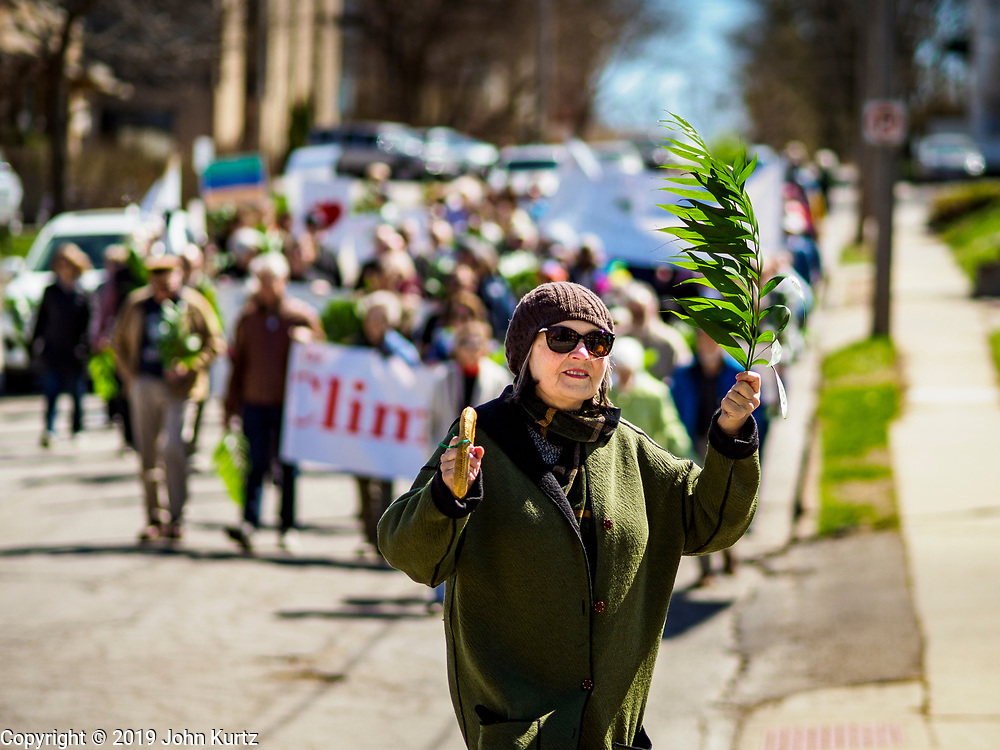 """14 APRIL 2019 - DES MOINES, IOWA: A woman carries a palm in the Palm Sunday procession for peace in Des Moines. About 200 people participated in an interdenominational  Palm Sunday procession calling for peace. The theme of the procession was """"To Love and Defend our Sacred Earth"""" and it was sponsored by Des Moines Faith Committee for Peace.     PHOTO BY JACK KURTZ"""
