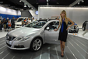 Israel, New model cars on display at a car show, Young female presenter attracting prospective buyers to a Volkswagen Passat. April 2008