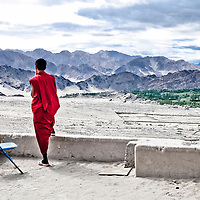 Ladakh, India - Luglio 2009: un monaco buddista contempla l'arido paesaggio montagnoso del Ladakh dalla terrazza di un monastero.<br /> <br /> Ladakh, India - July 2009: a Buddhist monk contemplating the mountainous view from the terrace of a monastery.