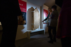 © Licensed to London News Pictures 25/01/2016, Cirencester, UK. Museum staff look at a unique Roman tombstone, found in February 2015, here on display for the first time at Corinium Museum in Cirencester. The tombstone was found near skeletal remains thought to belong to the person named on its inscription, making the discovery unique. After being found during excavation works on a former site of a garage, archaeologists said they believed it marked the grave of a 27-year-old woman called Bodica. Other theories point to it possibly belonging to a couple - as skeletal remains of women were found nearby.<br />