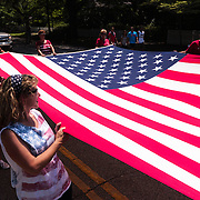 """Members of """"Oki Lovers"""" of Pittsburgh, PA carry an American Flag during the North Carolina 4th of July Festival Parade Friday July 4, 2014 in Southport, N.C."""