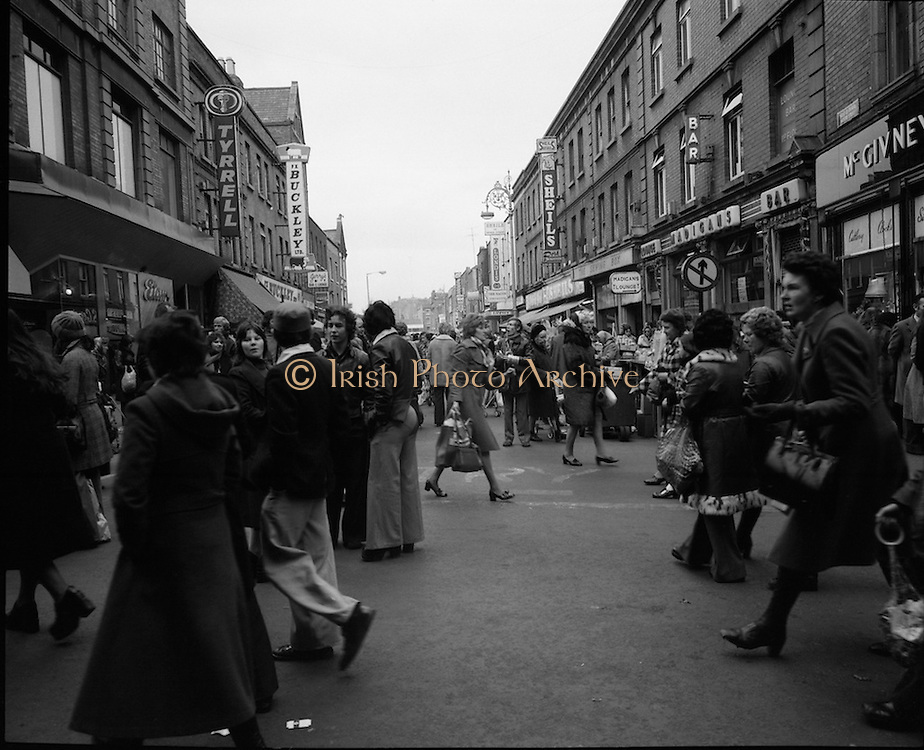Moore Street, Dublin.      (J97)..1975..23.12.1975..12.23.1975..23rd December 1975..For well over a hundred years Moore Street has served the citizens of Dublin. The longest running open air fruit and vegatable market offers value for money,particularly to those where money is in short supply. Predominately a fruit and veg market there are several traders who sell fish and seasonal goods, as illustrated by the photographs showing turkeys and holly wreaths being sold on the run up to Christmas..Image shows a general view down Moore Street from Henry Street as passers by hurry about their business.