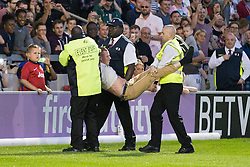 Image ©Licensed to i-Images Picture Agency. 07/08/2014. Salford, United Kingdom. Class of 92 Manchester. AJ Bell Stadium. Pitch invader carried off  . Class of 92 squad play Salford City FC at the AJ Bell Stadium . Picture by i-Images