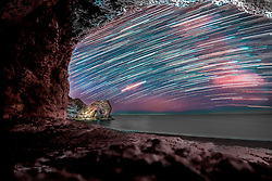 © Licensed to London News Pictures. 16/6/2018. Lulworth, UK. A long exposure comprised of over 200 exposures shows The Milky Way, framed by a cave, in sight of Durdle Daw at Lulworth in Dorset. Photo credit: Peter Scott/LNP