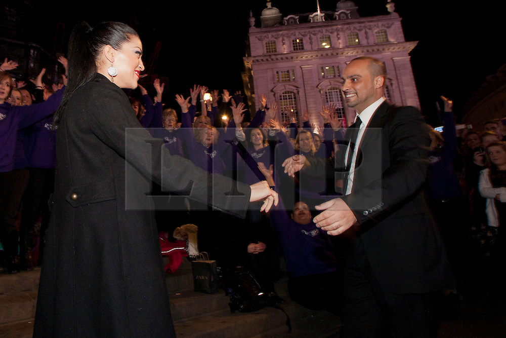 © Licensed to London News Pictures. 01/03/2012. London, UK.  Roger (unknown surname, pictured right) organised a singing flashmob in Piccadilly Circus tonight (01/03) to propose to his girlfriend Gina (pictured left) with a professional choir of around 100 singers and over 200 'facebook dancers' who sang 'Can't Take My Eyes Off You (I love you baby)' by Frankie Valli. Roger set up a secret event on facebook under the alias 'Romeo' to maintain secrecy. They have been dating for around a year, Gina said yes.  Photo credit : James Gourley/LNP
