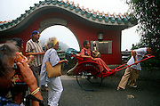 American tourists admire one of their number riding who has hired a rickshaw on Hong Kong's Peak.