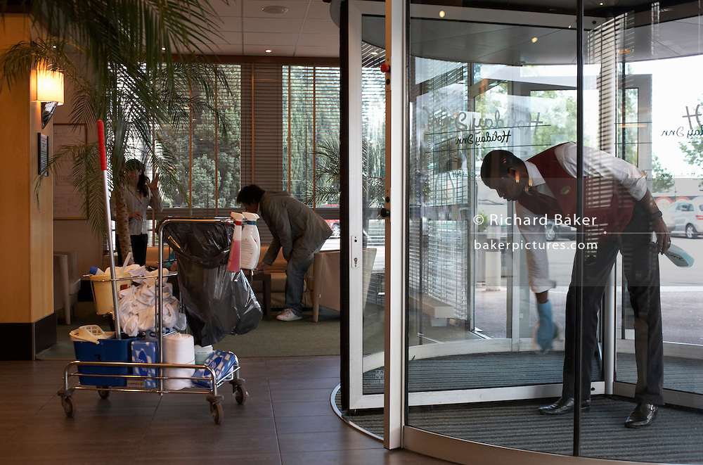 Wearing a company wastecoat and blue rubber gloves, the uniform of a Holiday Inn employee, a man of Black ethnicity bends forward to wipe the glass revolving doors at the entrance of this hotel in Paris. Nearby is the man's trolley containing janitorial cleaning products such as a mop and bucket, towels, cloth rolls, atomiser sprays, detergents and tissues needed to maintain the high standards of this motel chain. Coincidentally, a customer is also bending down to re-arrange something in her baggage and leaning at the same angle as the cleaner.