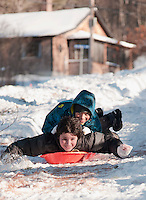 Cole Manion steers while Christian Pinkney enjoys the ride sliding from Stark Street on Tuesday after Monday's nor'easter brought a foot of snow to Laconia.  (Karen Bobotas/for the Laconia Daily Sun)