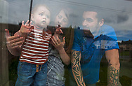 Victoria Cunningham, her husband Simon Giles and their son Oliver-James Giles look out from the window of the house the family rents in Bradford, Great Britain Monday, May 26, 2014. Through Save the Children's EAT, SLEEP, LEARN AND PLAY programme the family was awarded a fridge freezer and a toy and book pack. A record five million children in the UK could be trapped in poverty by 2020, according to new research by Save the Children. The report reveals that children have paid the highest price in the recession, with families having been hit by years of flat wages, cut to benefits and the rising cost of living. (Elizabeth Dalziel for Save the Children )