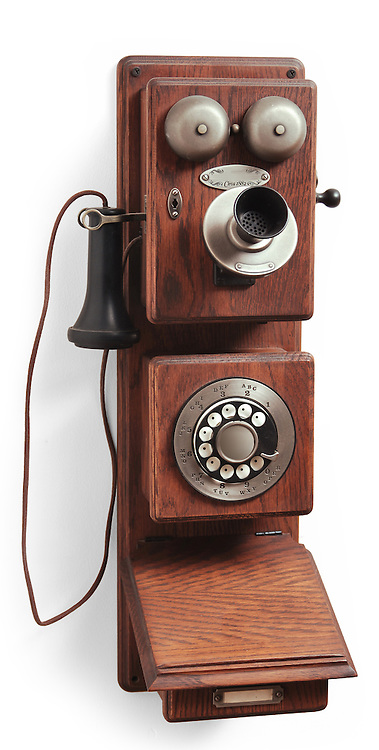 antique crank rotary telephone on white backtground