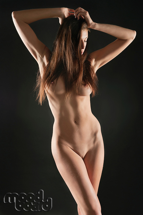 Young naked woman with hands in hair over black background