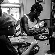 Desmond Gordon soothes his baby girl, Rosalie, while his family eats dinner. Desmond is a father of four, three girls and one 16 month old boy.