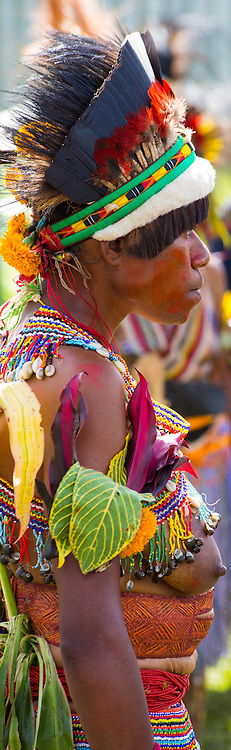 Side view portrait of a woman from the Bena region dressed in traditional Bena tribal dress for the Goroka Show, an annual Singsing Festival in the highlands of Papua New Guinea. She is wearing a colourful beaded shoulder vest  and her headdress is adorned with birds feathers and flowers.