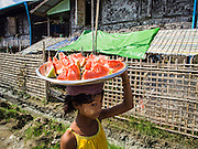 11 NOVEMBER 2014 - SITTWE, MYANMAR: A girl selling watermelon slices walks through the Rakhine Buddhist IDP camp near Sittwe. About 700 Rakhine Buddhist families live in an Internal Displaced Persons (IDP) camp on the edge of Sittwe. The people in the camp lost their homes in Sittwe in 2012 when Buddhist mobs rioted and burnt down Rohingya Muslim homes and businesses. The Buddhists' homes were mistakenly destroyed by other Buddhists or intentionally destroyed by retaliating Muslims during the 2012 violence. Unlike the Muslims, who live in much larger camps further from Sittwe, the Buddhists are allowed to come and go into downtown Sittwe and their homes are built in the traditional style, on stilts with large windows, and so are much more comfortable.   PHOTO BY JACK KURTZ
